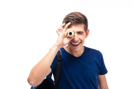 Smiling male student looking at camera through money isolated on a white background photo