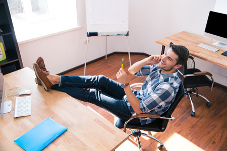 Happy businessman sitting on the office chair and talking on the phone in office