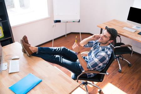 persona sentada: Hombre de negocios feliz sentado en la silla de oficina y hablando por tel�fono en la oficina