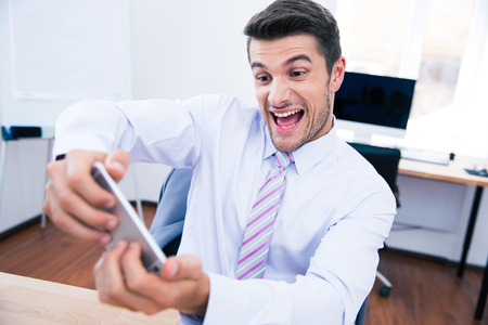 Funny businessman playing in game on the phone in office