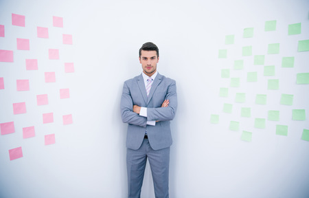 folded arms: Handsome businessman with arms folded standing near wall with stickers in office Stock Photo