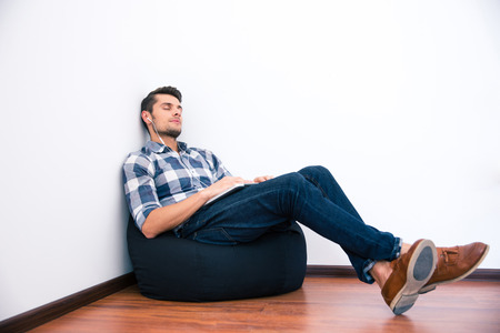 Casual man resting on the bag chair with headphones photo