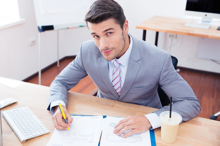 executive job search: Handsome businessman signing document in office and looking at camera