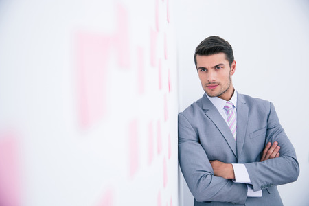 arms folded: Confident businessman with arms folded leaning on the wall with stickers in office Stock Photo