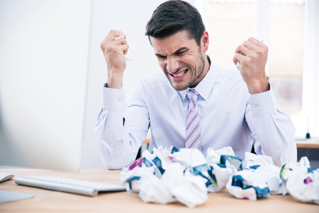 anger: Upset businessman sitting at the table with crumpled paper in office