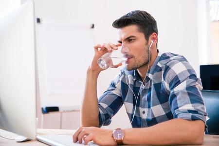 캐주얼 천으로 잘 생긴 사업가 PC를 사용하고 사무실에서 마시는 물