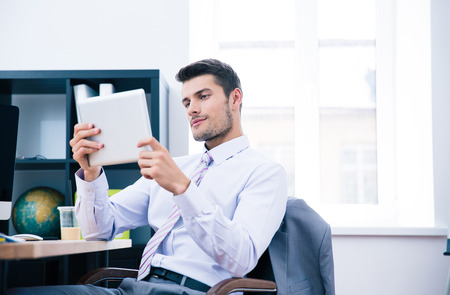 Confident businessman sitting at the table and using tablet computer in office photo