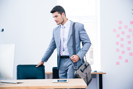 relaxed business man: Portrait of a confident businessman with bag standing in office
