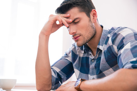 headache: Casual businessman sitting at the table with headache in office