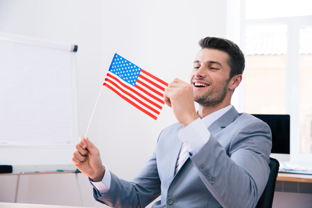 american table: Cheerful handsome businessman holding USA flag in office Stock Photo