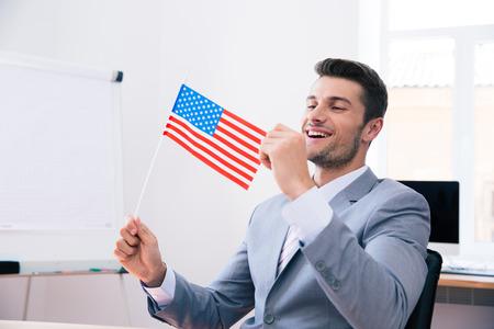 personen: Vrolijke knappe zakenman die vlag van de VS in het kantoor