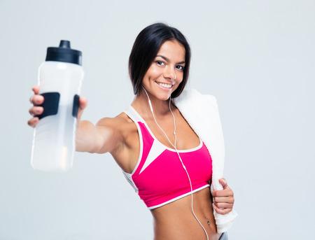 Mujer feliz de la aptitud que sostiene la botella de agua sobre fondo gris. Mirando a la cámara