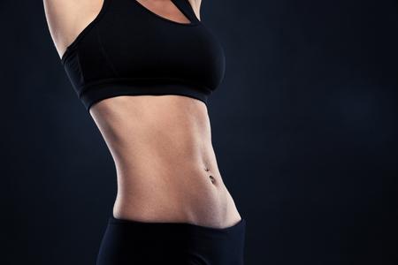 Primer plano de los abdominales de una mujer en forma aislado sobre fondo negro Foto de archivo