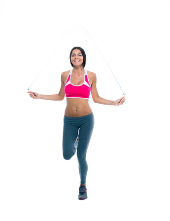 Full length portrait of a sports woman workout with skipping rope isolated on a white background photo