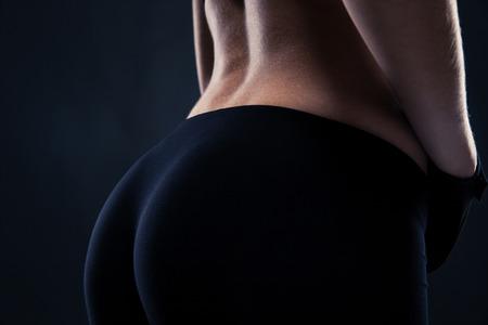 黒の背景にフィットネスの女性の尻のポートレート、クローズ アップ