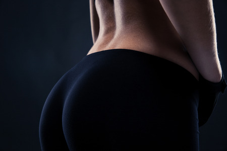 ass standing: Closeup portrait of a fitness female buttocks over black background