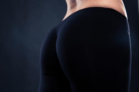 Close-up portret van een fitness vrouwelijke billen op een zwarte achtergrond