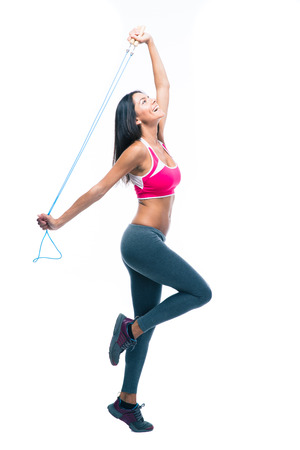Full length portrait of a smiling fitness woman stretching with skipping rope isolated on a white background and looking up photo