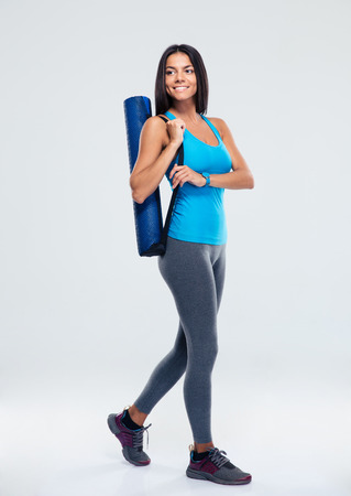 woman full body: Full length portrait of a smiling sports woman with yoga mat walking over gray background. Looking away