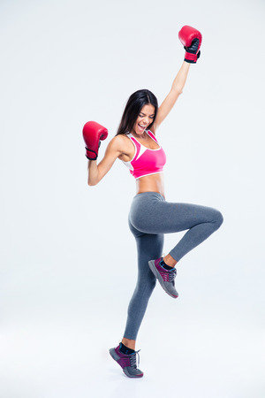 Full length portrait of a fitness woman in boxing gloves celebrating her success over gray background photo