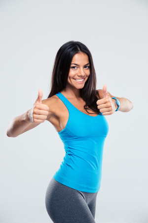 Smiling sporty woman showing thumb up sign over gray background. Looking at camera 版權商用圖片