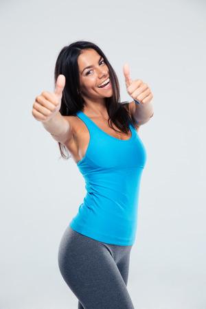笑顔の女性は、灰色の背景の上のサインを親指を示します。カメラを目線