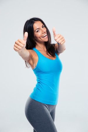fitness girl: Smiling woman showing thumb up sign over gray background. Looking at camera