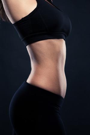 Retrato de detalle de un cuerpo perfecto mujeres `s sobre fondo negro Foto de archivo