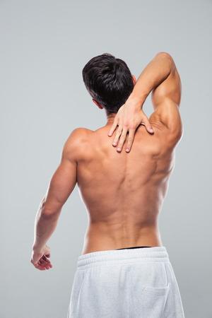 dolor: Vista trasera retrato de un hombre musculoso con dolor de cuello sobre fondo gris