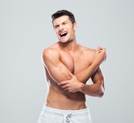 codo: Retrato de un hombre que tiene dolor en el codo sobre fondo gris