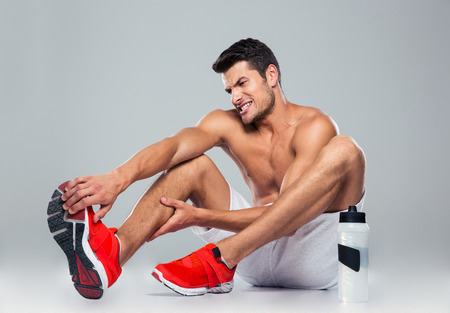 painful: Portrait of a fitness man with foot pain over gray background Stock Photo