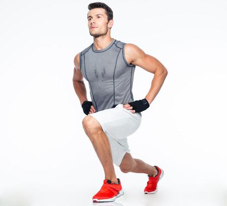 In voller Länge Portrait eines Fitness-Mann streckte auf einem weißen Hintergrund
