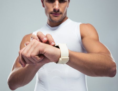 sport background: Closeup portrait of a fitness man using smartwatch