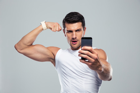 Sport man die selfie foto op de smartphone over grijze achtergrond Stockfoto
