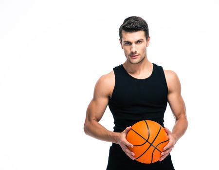 baloncesto: Retrato de un jugador de baloncesto de pie con bola aislado en un fondo blanco. Mirando a la cámara