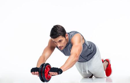 Man tập luyện với bánh xe tập thể dục trên tầng bị cô lập trên một nền trắng