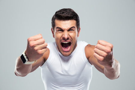 Excited fitness man shouting at camera over gray background Banque d'images