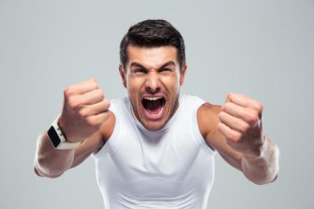 Opgewonden fitness man schreeuwen naar de camera over grijze achtergrond