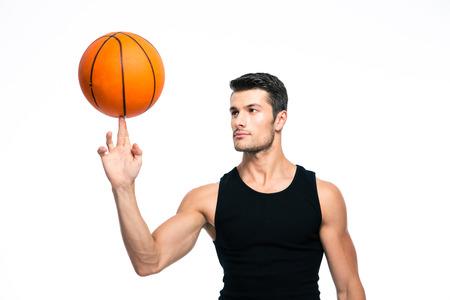 baloncesto: Jugador de baloncesto de giro bola en su dedo aislado en un fondo blanco