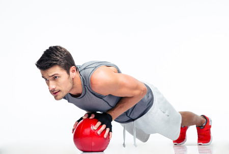 sports backgrounds: Sports man working out with fitness ball isolated on a white background
