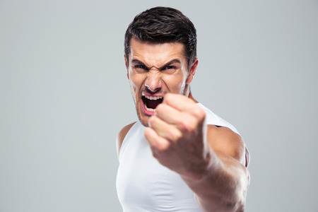 Angry man screaming and showing fist over gray background Фото со стока