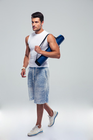 power yoga: Full length portrait of a fitness man walking with yoga mat over gray background