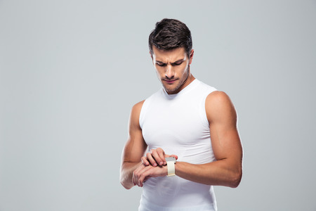 watch over: Handsome sports man using smart watch over gray background
