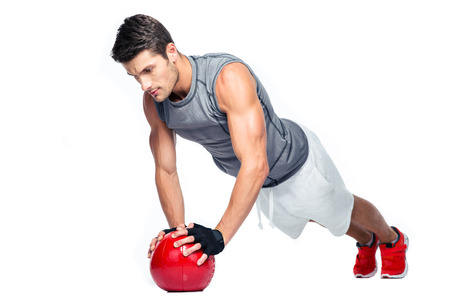 boy shorts: Sports man working out with fitness ball isolated on a white background