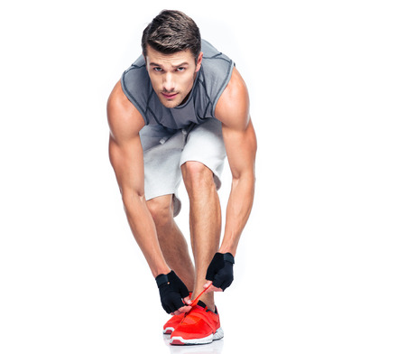 Fitness man tie shoelaces isolated on a white background. Looking at camera
