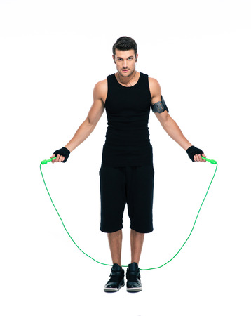 rope: Full length portrait of a handsome man jumping with skipping rope isolated on a white background. Looking at camera Stock Photo