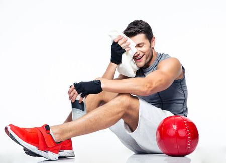 fitness hombres: Feliz el hombre de la aptitud que se reclina sobre el suelo aislado en un fondo blanco Foto de archivo