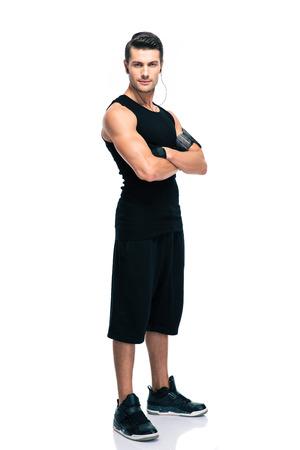 Pleine longueur portrait d'un homme de remise en forme, debout avec les bras croisés isolé sur un fond blanc. Regardant l'objectif