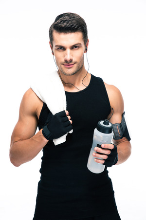フィットネス: ハンサムなフィットネス男は白い背景に分離された水とタオルとボトルを保持しています。カメラを目線