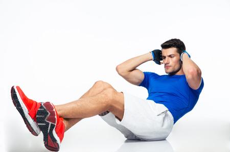 Fitness man doet buikspieroefeningen geïsoleerd op een witte achtergrond Stockfoto